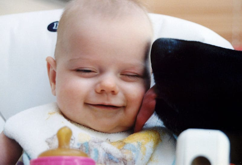 Baby smiles when licked by the family dog