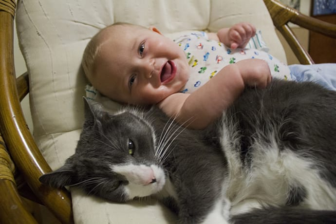 Baby and cat smile for the camera