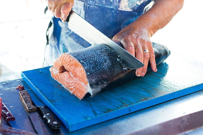 Man's filleting a raw fish on the table