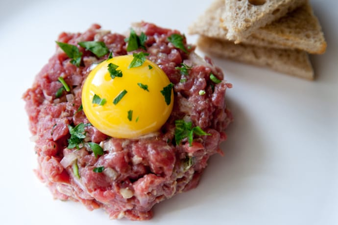 raw meat with an egg and toast