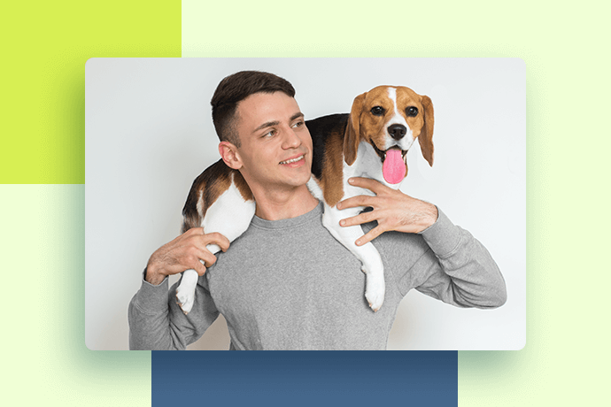Young man holding a Beagle on his shoulders